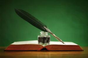 Quill pen and inkwell resting on an old book with green backgrou